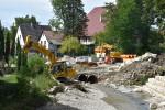 Bauarbeiten im Betzinger Gaasgarten: Ein Bagger, ein weiteres Baustellenfahrzeug und Baumaterialien am Ufer der Echaz